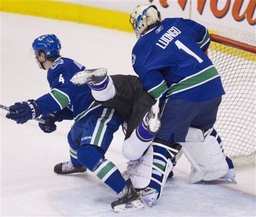 Los Angeles Kings center Michal Handzus (26) tries to get a shot past Vancouver Canucks goalie Roberto Luongo (1) and defenseman Keith Ballard (4) during first period NHL hockey action at Rogers arena in Vancouver, British Columbia, Thursday, March 31, 2011. (AP Photo/The Canadian Press, Jonathan H