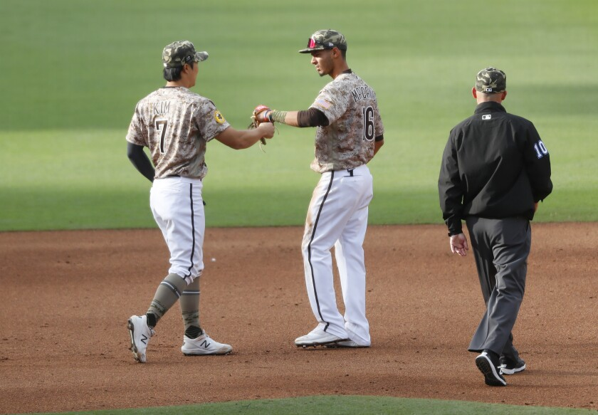 Ha-Seong Kim and Tucupita Marcano celebrate a Padres double play against the St. Louis Cardinals on Sunday at Petco Park.