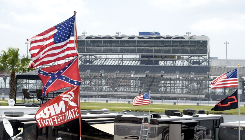 FILE - In this July 4, 2015, file photo, confederate and American flags fly on top of motor homes at Daytona International Speedway in Daytona Beach, Fla. Bubba Wallace, the only African-American driver in the top tier of NASCAR, calls for a ban on the Confederate flag in the sport that is deeply rooted in the South. (AP Photo/Phelan M. Ebenhack, File)