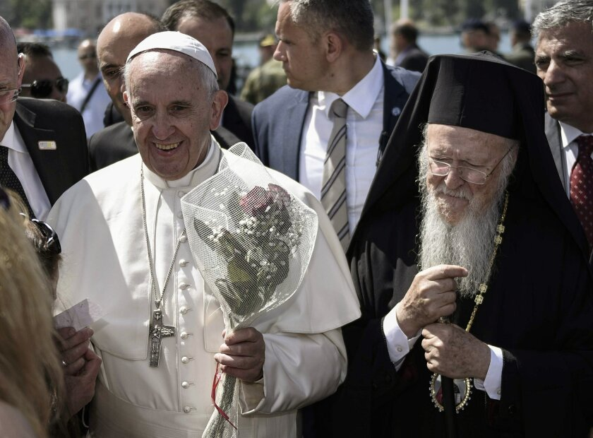 FILE - In this file photo dated Saturday, April 16, 2016, released by Greek Prime Minister's office, Pope Francis, left, is escorted by Ecumenical Patriarch Bartholomew I, during a visit to the Greek island of Lesbos. On Friday June 3, 2016, the Orthodox Church led by Patriarch Bartholomew I, issue
