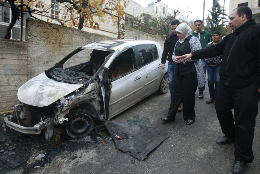 Palestinian Dr. Laila Ghannam, the governor of Ramallah and al-Bireh, inspects an area attacked by suspected Jewish settlers in the Jalazoun refugee camp north of Ramallah, Tuesday, Dec. 31, 2013.  Israeli police say suspected Jewish vandals set fire to three vehicles in the West Bank early Tuesday