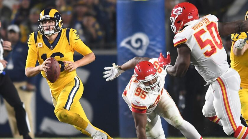 Rams quarterback Jared Goff scrambles away form Chiefs defenders Chris Jones (95) and Justin Houston in the second quarter at the Coliseum.