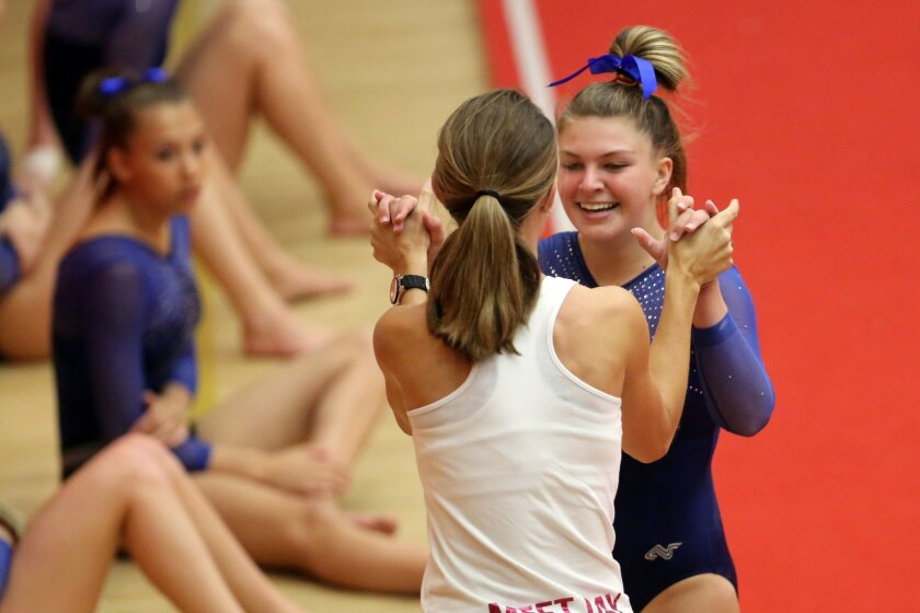 In a photo earlier this season, Grace Azinger of La Costa Canyon is congratulated by coach Jessica Garrett after her floor exercise routine. On Friday, the Mavericks defeated Del Norte in gymnastics.