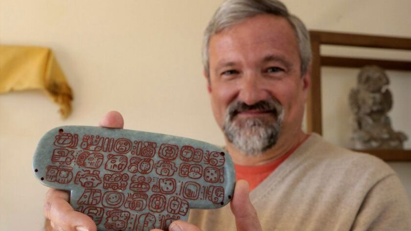 Archaeologist Geoffrey Braswell holds a replica of the jade Maya pendant unearthed in Belize.