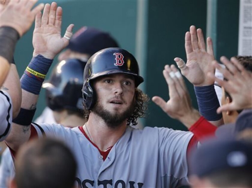 Boston Red Sox's Jarrod Saltalamacchia is congratulated in the dugout after scoring on a Will Middlebrooks single in the fourth inning of a baseball game against the Kansas City Royals at Kauffman Stadium in Kansas City, Mo., Saturday, Aug. 10, 2013. (AP Photo/Colin E. Braley)
