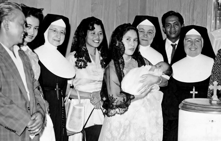 Joe Lumarda in his mother's arms at his christening, with family members and nuns by their side