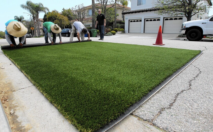 Workers on a turf removal and replacement job install artificial grass at a Pacific Palisades home.
