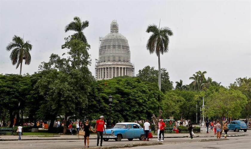 Tránsito de personas y vehículos en calle aledaña al Parque de la Fraternidad en La Habana (Cuba). EFE/Archivo