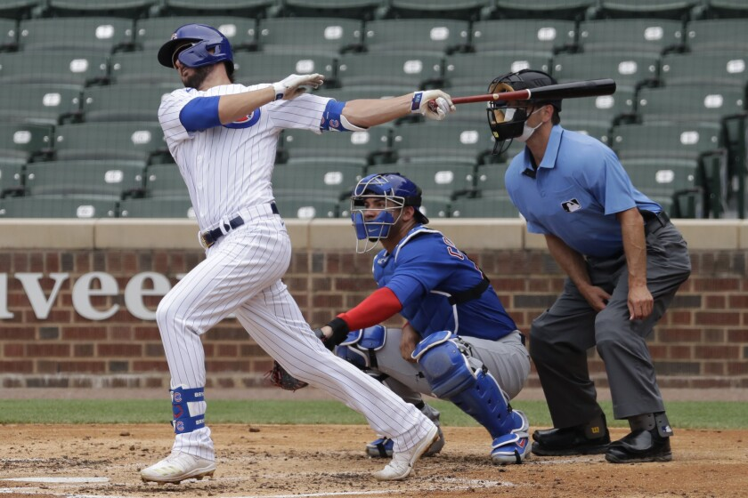 FILE - In his July 15, 2020, file photo, Chicago Cubs' Kris Bryant, left, hits a one-run single during an intrasquad baseball game at Wrigley Field in Chicago. As baseball attempts to play a shortened 60-game regular season amid a coronavirus pandemic, there is some concern that home plate could become a hot spot for transmission. (AP Photo/Nam Y. Huh, File)