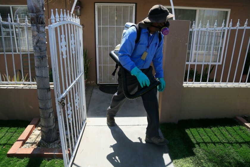 Sean Simmons, a vector control technician, moves on after spraying for the Zika virus at a home in the Mount Hope neighborhood where the county of San Diego sprayed a two-block area because of a suspected case of Zika infection.
