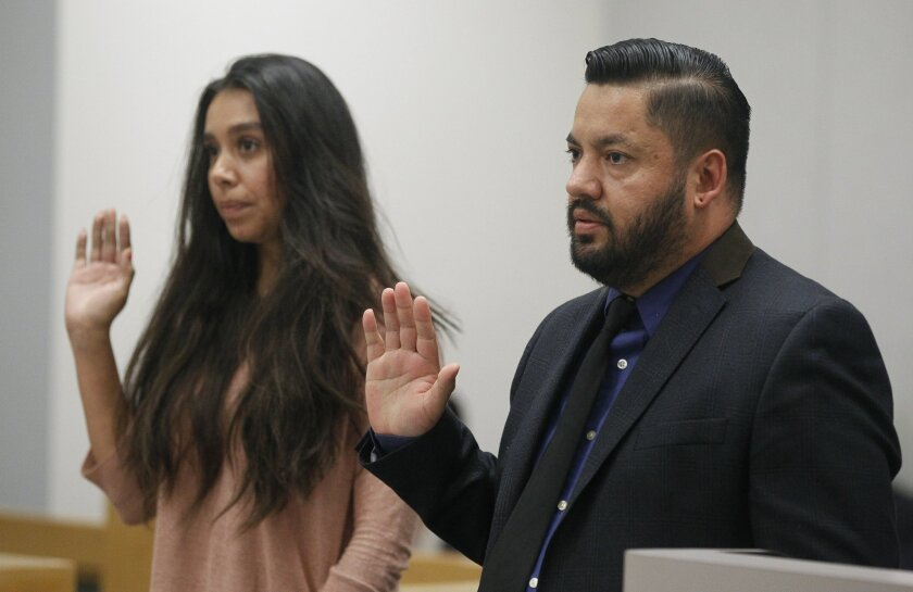 Rebecca Gonzalez, 32, and Jose Torres, 36, who have been married for 12 years, raise their hands as they are sworn in during their one-day divorce proceeding at the Madge Bradley Courthouse in San Diego on Thursday.