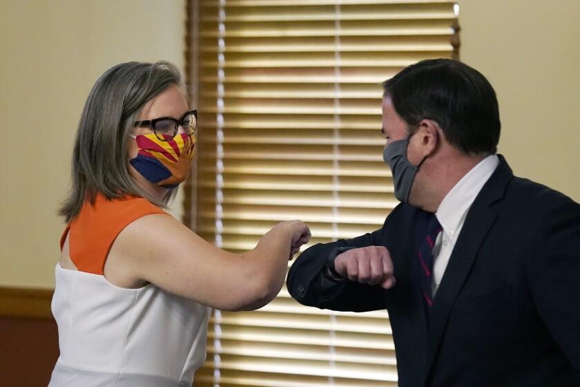 Arizona Secretary of State Katie Hobbs, left, and Arizona Gov. Doug Ducey bump elbows.
