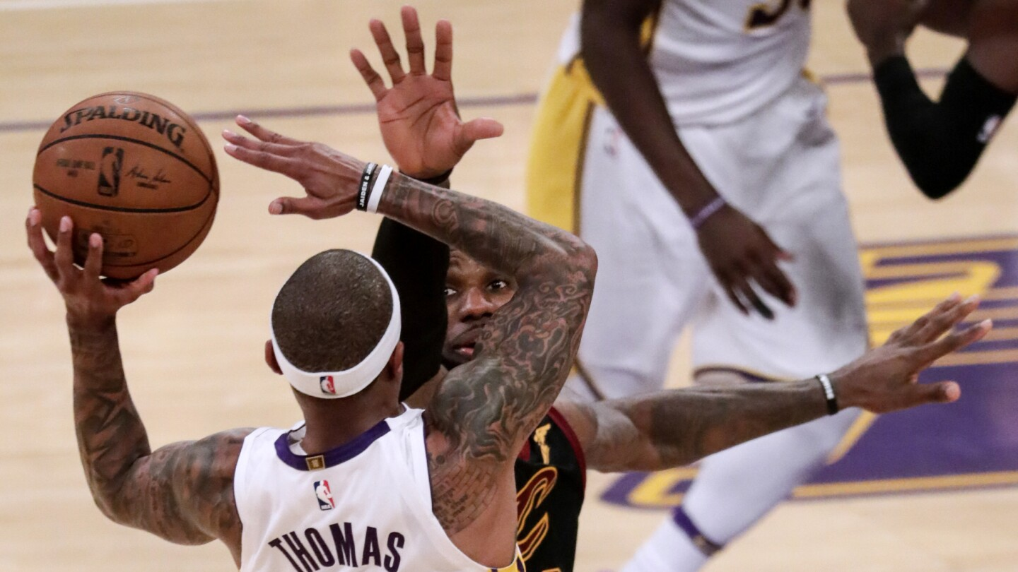 Lakers guard Isaiah Thomas shoots over Cavaliers forward LeBron James during fourth quarter action.