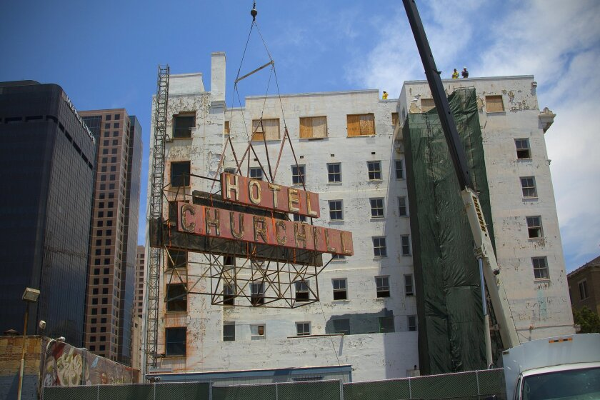 The Hotel Churchill neon sign is lowered from the seventh floor of the 101-year-old downtown building so it can be repaired and restored before being reinstalled next year.