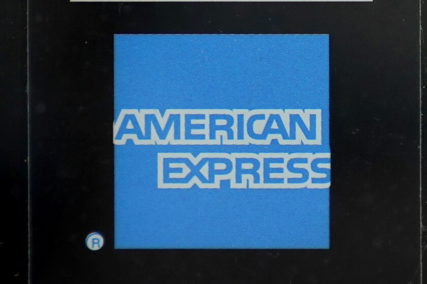 An American Express logo is attached to a door in Boston's Seaport District, Wednesday, July 21, 2021. American Express Co.'s second-quarter revenue surged as people started spending more at a time when many are getting vaccinated against COVID-19 and feel more comfortable going out to restaurants, shops and entertainment venues again. (AP Photo/Steven Senne)