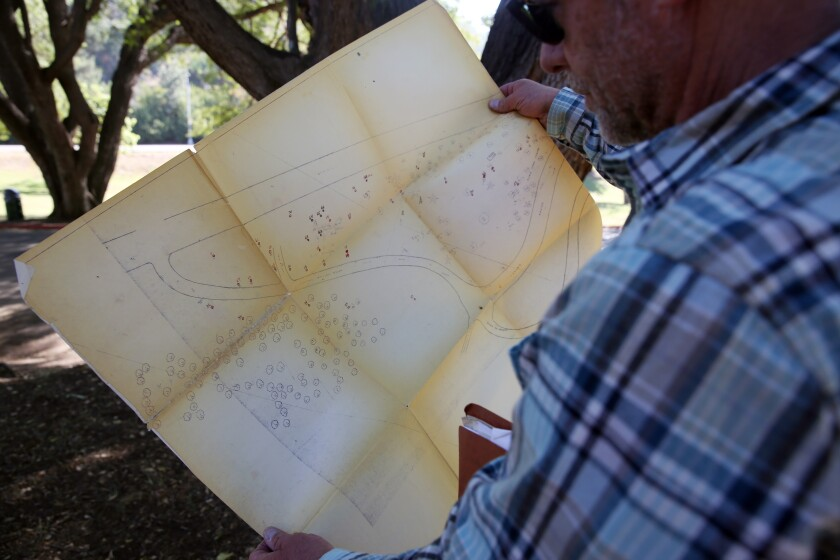 L.A. arborist Leon Boroditsky holds a hand-made map of the oldest trees in Elysian Park's arboretum.