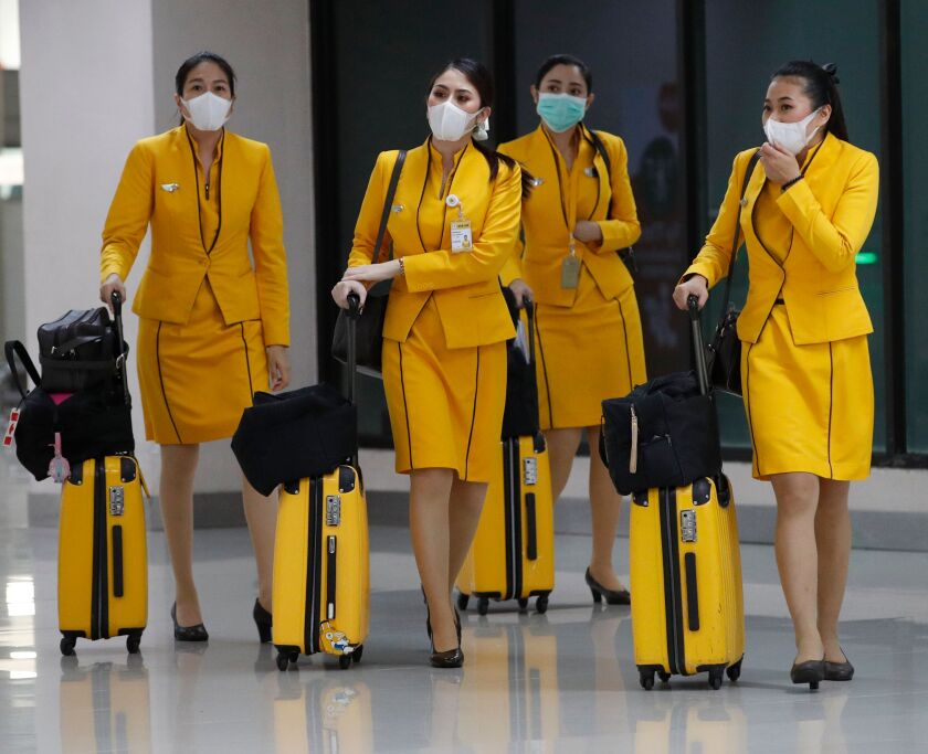 Flight attendants wearing face masks and yellow uniforms with rolling yellow suitcases arrive at Don Mueang Airport in Bangkok, Thailand.