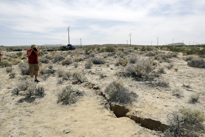 A visitor takes a photo of a crack in the ground following earthquakes near Ridgecrest, California.