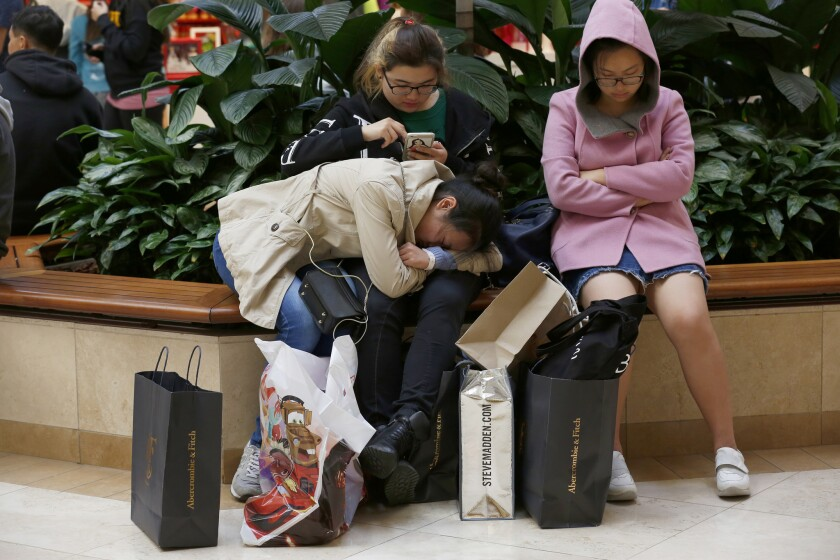 Southern California shoppers said crowds seem calmer this year on Black Friday. At South Coast Plaza, Mandy Zhao, 20, left, Mia Hou, 19 and Keer Xu, right, rest after shopping since 2 a.m. Friday.