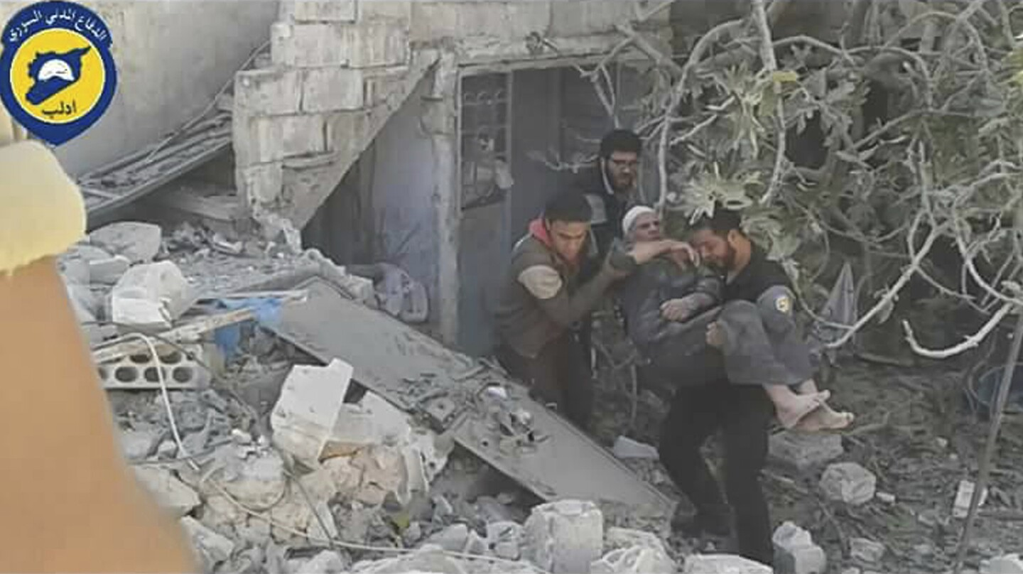 In this photo provided by the Syrian Civil Defense group known as the White Helmets, Syrian Civil Defense workers help an injured man after airstrikes in the village of Hass in the Idlib province of Syria on Oct. 26, 2016.