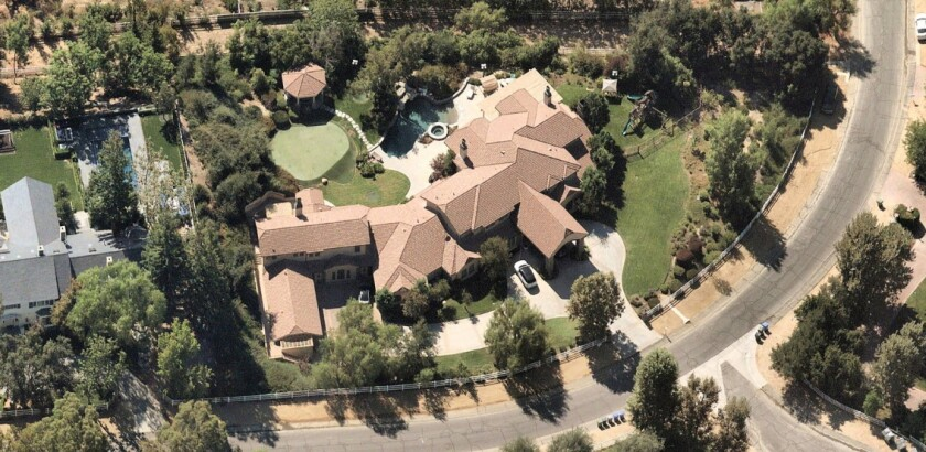 The almost 12,000-square-foot home sits on about 1.5 acres in guard-gated Hidden Hills.