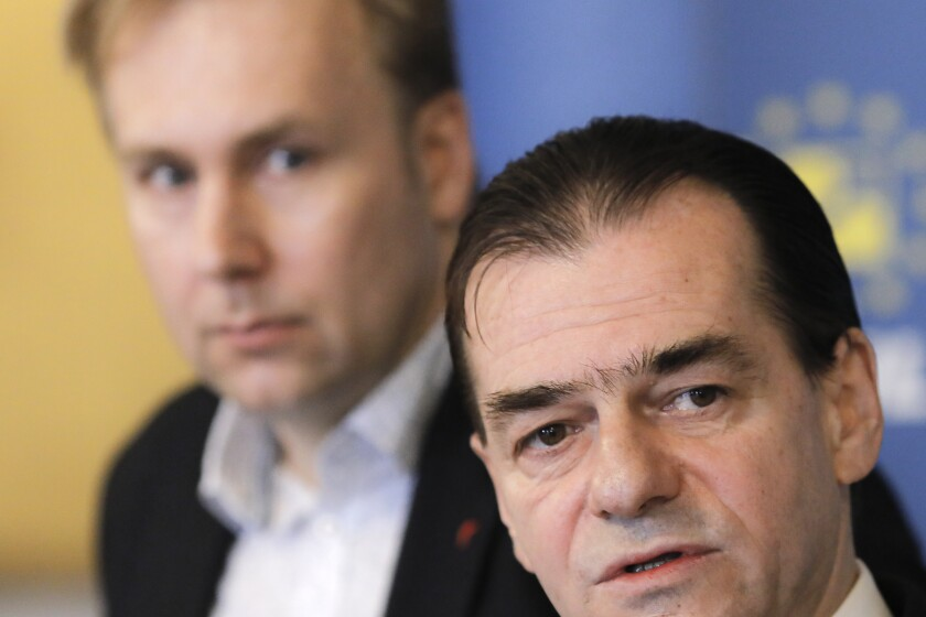 Romania's health minister Victor Costache, left, watches as caretaker prime minister of Romania, Ludovic Orban speaks during a press conference in Bucharest, Romania, Friday, March 13, 2020 after it was confirmed that a senator who attended several meetings in the building tested positive for the infection. The caretaker prime minister of Romania, Ludovic Orban, said in a press conference at the parliament, the government, including all ministers, as well as the leadership of the ruling National Liberal Party and all its senators, are going into quarantine after one of the governing party's senators, who took part in high-level meetings, who confirmed to be infected with the coronavirus. (AP Photo/George Calin)