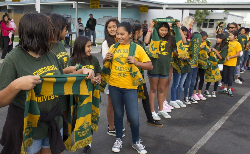 Students from Hilary Fenn's sixth-grade class at Sonora Elementary School in Costa Mesa receive green and gold Concordia University scarves brought by retired Concordia professor Martin Schramm on Friday. Sonora participates in the nationwide No Excuses University program promoting college readiness.