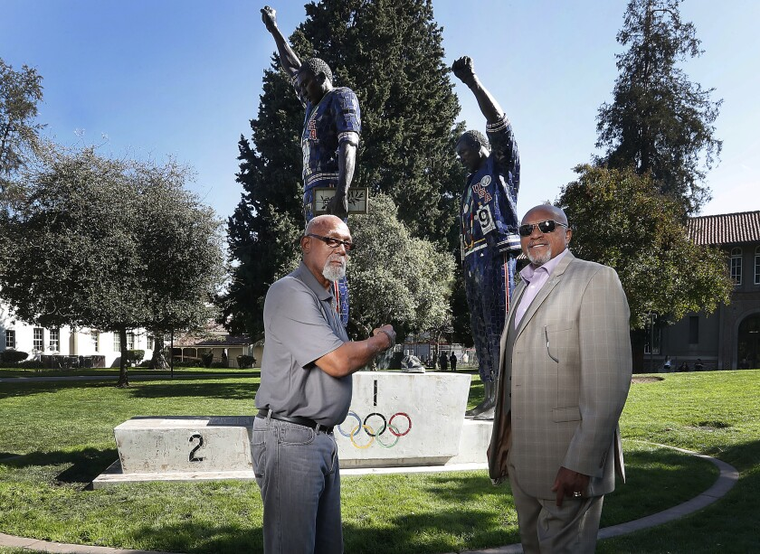 John Carlos and Tommie Smith pose for a photo in front of statue that honors their iconic protest at the 1968 Olympic Games.