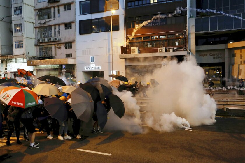 Protesters in Hong Kong use umbrellas to shield themselves from tear gas fired by police as they face off on a street.