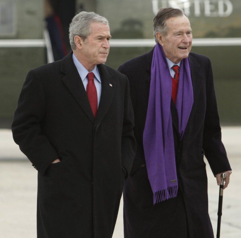 Private photos of presidents George W. Bush, left, and his father George H.W. Bush were hacked and put online.
