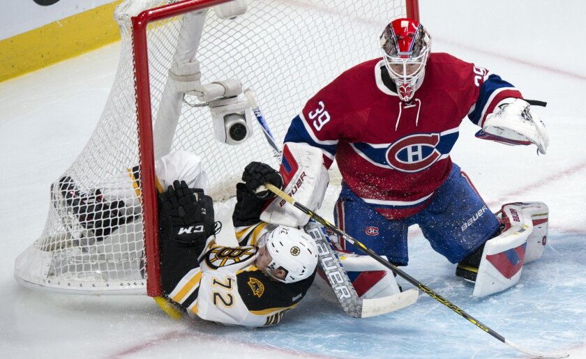 Boston Bruins' Frank Vatrano (72) slides into the net as Montreal Canadiens' goalie Mike Condon defends the crease during second period NHL hockey action, in Montreal, on Saturday, Nov. 7, 2015. (Paul Chiasson/The Canadian Press via AP)