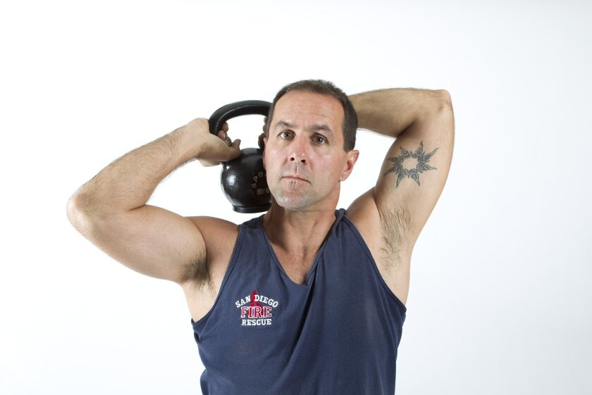 San Diego firefighter Kevin Melanson performs kettlebell halos to warm up his shoulders.