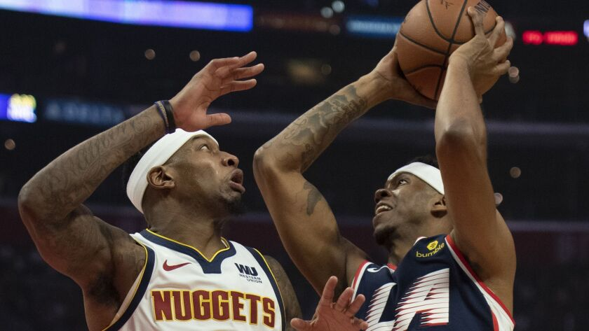 Los Angeles Clippers guard Tyrone Wallace, right, goes up to the basket under pressure as Denver Nug