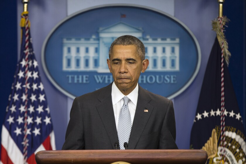 President Obama pauses as he speaks about the attacks in Paris during a White House news conference on Friday.