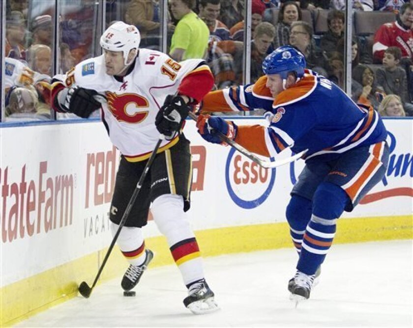 Calgary Flames Brian McGrattan (16) is checked by Edmonton Oilers Ryan Whitney (6) during first period NHL hockey action in Edmonton, Alberta, on Monday April 1, 2013. (AP Photo/The Canadian Press, Jason Franson)