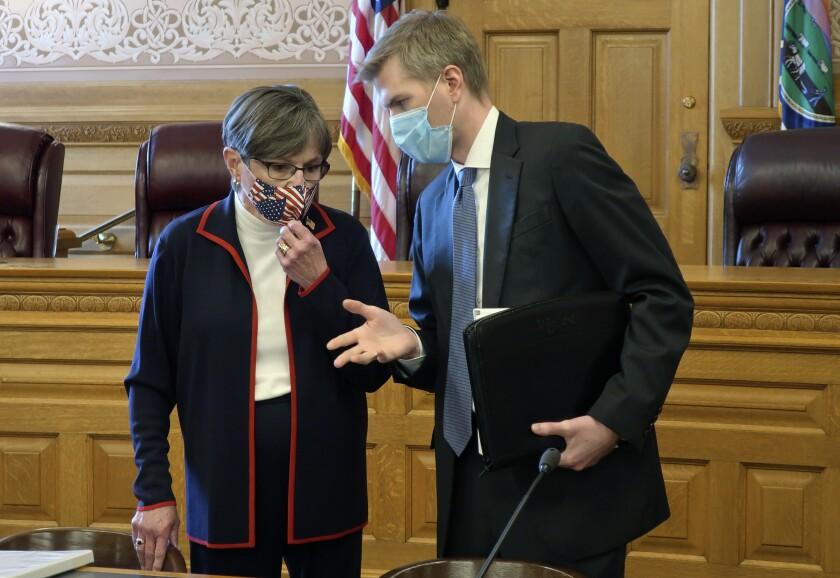 La gobernadora de Kansas Laura Kelly habla con Clay Britton, su abogado principal, previo a una reunión con líderes del Congreso estatal, el jueves 2 de julio de 2020, en Topeka, Kansas. (AP Foto/John Hanna)