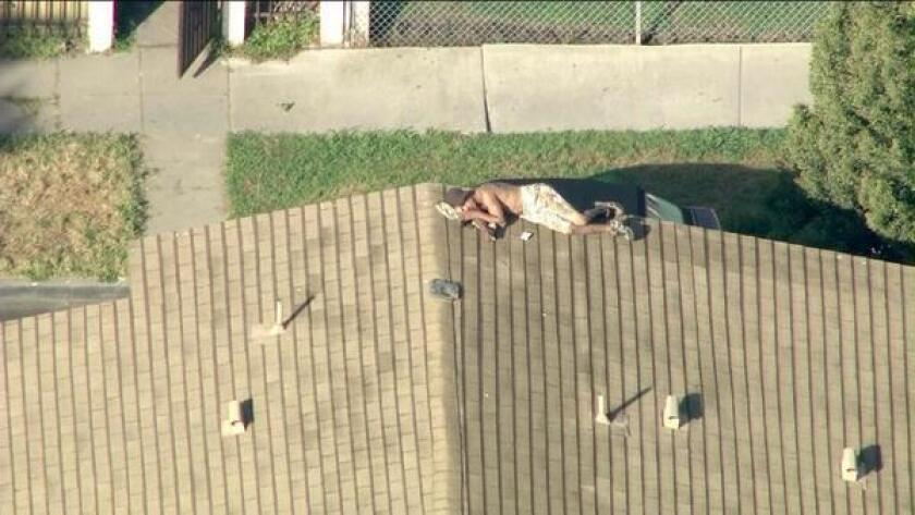 Los Angeles police surrounded a home Friday morning in Venice, where a shirtless burglary suspect was perched on a rooftop.