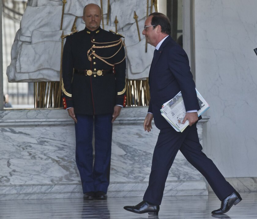 French President Francois Hollande walks through the lobby of the Elysee Palace in Paris, France, after the weekly cabinet meeting Wednesday, Aug. 26, 2015. (AP Photo/Michel Euler)