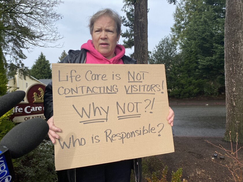 Cheri Chandler holds sign outside Life Care Center of Kirkland