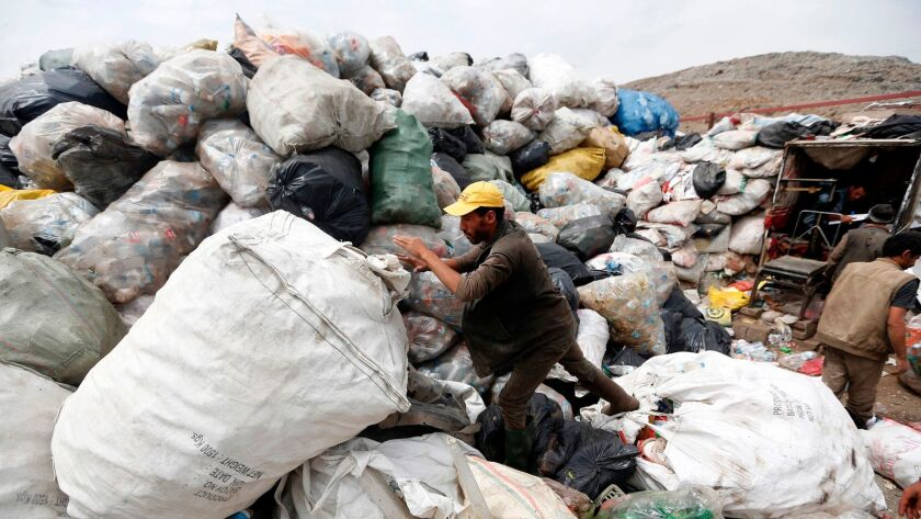 A Yemeni man scavenges for recyclable items at a garbage dump on the outskirts of the Yemeni capital