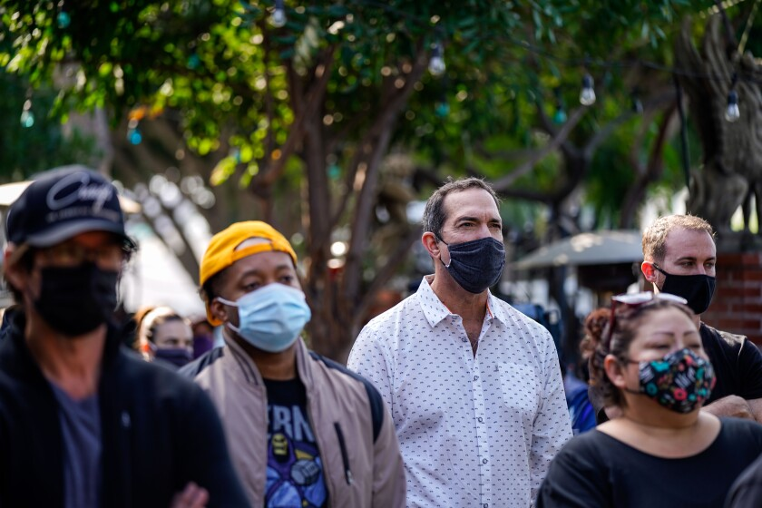 A woman and a girl in protective masks walk in the MacArthur Park area.