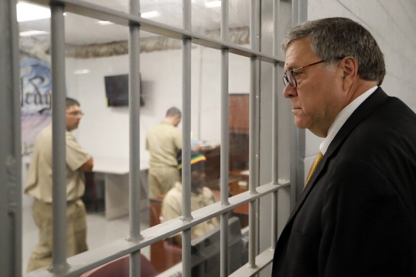 FILE - In this July 8, 2019, file photo, Attorney General William Barr watches as inmates work in a computer class during a tour of a federal prison. in Edgefield, S.C. The Justice Department is making changes to its system used to identify whether an inmate is likely to commit crimes again after release from prison to ensure the process is fair and effective. It's part of a sweeping criminal justice overhaul measure that was enacted last year. The federal Bureau of Prisons has already assessed nearly all of the 175,269 inmates in federal custody. But the Justice Department plans to re-screen all of those inmates under new guidelines, which officials say places a stronger emphasis on accurately measuring an inmate's change behind bars. (AP Photo/John Bazemore, File)