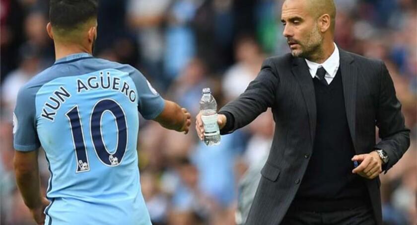 Pep Guardiola (d), entrenador del City, da agua al delantero Sergio 'Kun'' Agüero, quien anotó para los Citizens.