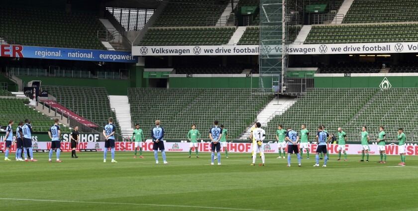 Players stand during a minute's silence for the victims of the coronavirus before a Bundesliga game between Werder Bremen and Borussia Moenchengladbach on May 26, 2020.