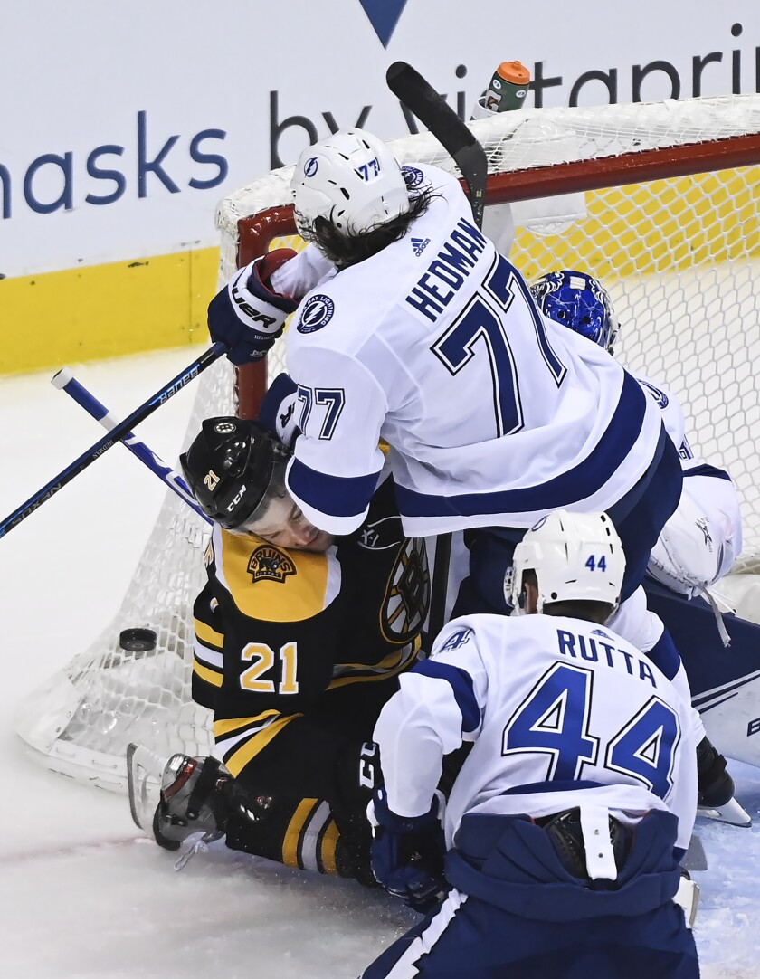 Tampa Bay Lightning defenseman Victor Hedman (77) takes out Boston Bruins left wing Nick Ritchie (21) during the third period of an NHL hockey playoff game Wednesday, Aug. 5, 2020 in Toronto. (Nathan Denette/The Canadian Press via AP)
