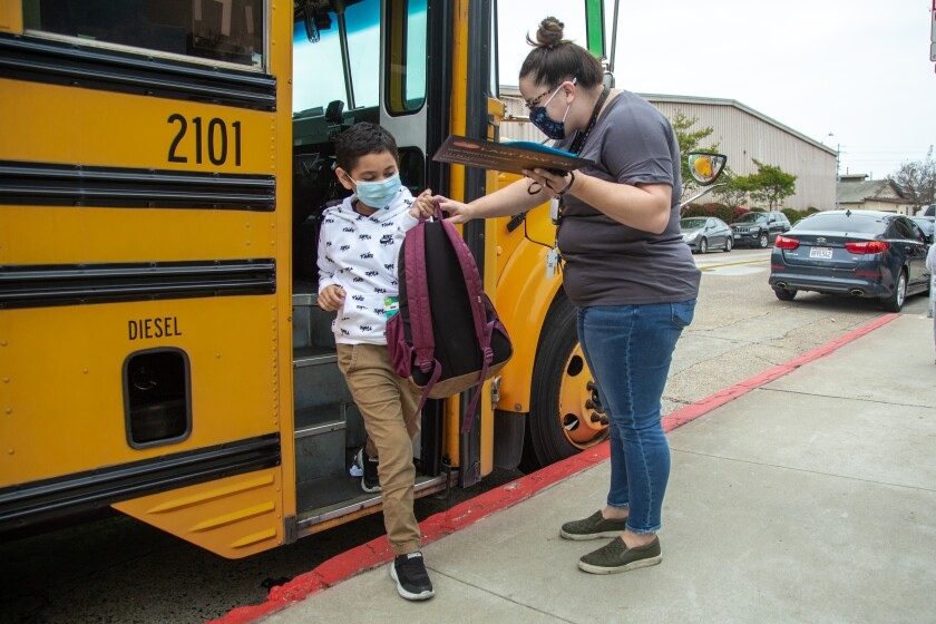 A teacher welcomes Jesus Maganda as he steps off the bus in April.