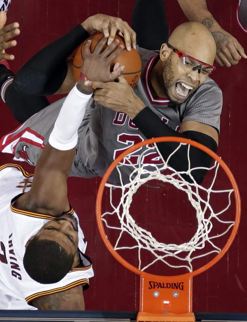 Chicago Bulls' Taj Gibson, right, is stopped by Cleveland Cavaliers' Kyrie Irving (2) on a drive to the basket during the first half of an NBA basketball game Saturday, Jan. 23, 2016, in Cleveland. (AP Photo/Tony Dejak)