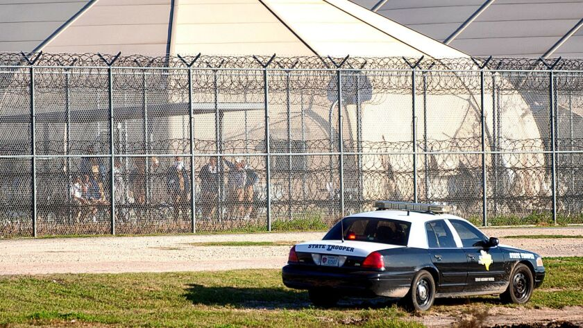 Prisoners stand at the western fence as law enforcement officials converge on the Willacy County Correctional Center in Raymondville, Texas, in response to a prisoner uprising in 2015.
