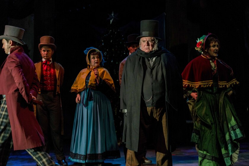 "Tom Stephenson (front right) as Ebenezer Scrooge, and the cast of Cygnet Theatre's ""A Christmas Carol."""