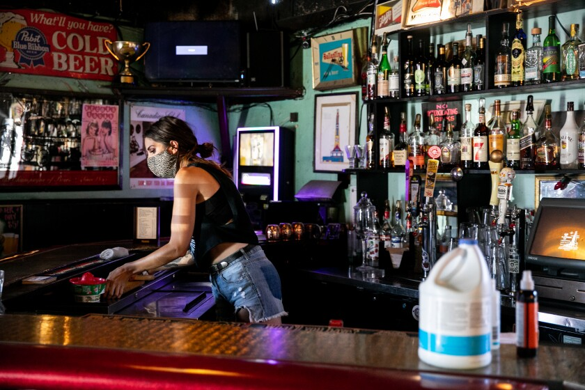 Jenna O'Brien, a bartender at The Tower Bar, preps the bar on the first day it was open after shuttering for months.